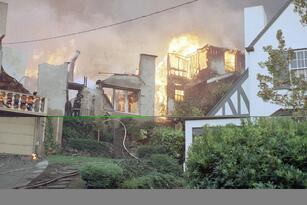 Firefighters spray water on the remains of a burning house in the Rockridge area of Oakland, California on Sunday, Oct. 20, 1991. Hundreds of homes were destroyed by the blaze. (AP Photo/Glenn Morimoto)