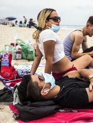 MIAMI BEACH, FL - JUNE, 19: Daniel Milian, from right, Miguel Martinez, and Laura De Armas chat as they relax on South Beach in Miami Beach, FL on Friday, June 19, 2020. Miami Beach reopened on June 10th after being shutdown due to the Covid-19 pandemic. (Photo by Scott McIntyre/For The Washington Post via Getty Images)