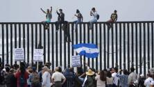 Varios inmigrantes escalan el muro fronterizo durante la protesta en apoyo de la caravana
