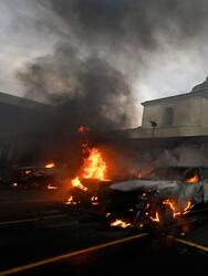 Firefighters try to extinguish a burning car at the Congress' parking, after former Guatemalan soldiers attempted to enter the Congress building while protesting in demand of compensation for their services during the country civil war (1960-1996), in Guatemala City on October 19, 2021. - Hundreds of former Guatemalan soldiers caused damage and burnt vehicles in the center of the capital while demanding compensation for their services, as the compensation law for victims of the civil war --widows and orphans-- does not include members of the armed forces. (Photo by JOHAN ORDONEZ / AFP) (Photo by JOHAN ORDONEZ/AFP via Getty Images)