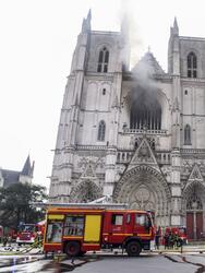 """A French Police officer gestures as firefighters are at work to put out a fire at the Saint-Pierre-et-Saint-Paul cathedral in Nantes, western France, on July 18, 2020. - The major fire that broke out on July 18, 2020 inside the cathedral in the western French city of Nantes has now been contained, emergency services said. """"It is a major fire,"""" the emergency operations centre said, adding that crews were alerted just before 08:00 am (0600 GMT) and that 60 firefighters had been dispatched. (Photo by Sebastien SALOM-GOMIS / AFP) (Photo by SEBASTIEN SALOM-GOMIS/AFP via Getty Images)"""