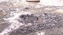 Un rayo deja un cráter humeante en la carretera y  un poste en llamas