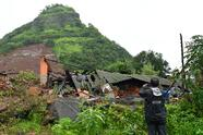 A man takes pictures of a landslide at Taliye, about 22 km from Mahad city on July 24, 2021, as the death toll from heavy monsoon rains climbed to 76, with nearly 90,000 others evacuated in the western state of Maharashtra. (Photo by INDRANIL MUKHERJEE / AFP) (Photo by INDRANIL MUKHERJEE/AFP via Getty Images)