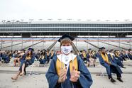 """FORT WORTH, TEXAS - MAY 21: Jeffrey McHugh sits six feet apart from classmates during Little Elm High School graduation ceremonies at Texas Motor Speedway on May 21, 2020 in Fort Worth, Texas. Texas Motor Speedway, which hosts NASCAR races, hosted graduation ceremonies for high schools from the Denton County area. Due to the coronavirus (COVID-19) pandemic family members were allowed to park on the racetrack infield and could watch the ceremony on the """"Big Hoss TV"""" screen on a live feed. (Photo by Ronald Martinez/Getty Images)"""