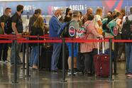 Travelers wait to check in at the delta ticket counter at Salt Lake City International Airport Tuesday, Aug. 17, 2021, in Salt Lake City. (AP Photo/Rick Bowmer)