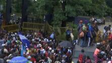 El momento en el que los migrantes de la caravana rompen la cerca en la frontera guatemalteca con México