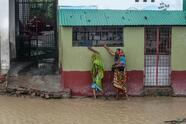 """Residents walk along a house on a flooded street heading to a shelter ahead of the expected landfall of cyclone Amphan, in Dacope of Khulna district on May 20, 2020. - Several million people were taking shelter and praying for the best on Wednesday as the Bay of Bengal's fiercest cyclone in decades roared towards Bangladesh and eastern India, with forecasts of a potentially devastating and deadly storm surge. Authorities have scrambled to evacuate low lying areas in the path of Amphan, which is only the second """"super cyclone"""" to form in the northeastern Indian Ocean since records began. (Photo by Munir uz Zaman / AFP) (Photo by MUNIR UZ ZAMAN/AFP via Getty Images)"""