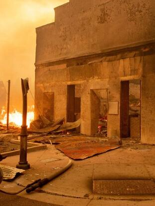 Battalion Chief Sergio Mora surveys a burned bar as the Dixie fire tears through downtown Greenville, California on August 4, 2021. - The Dixie fire burned through dozens of homes and businesses in downtown Greenville and continues to forge towards other residential communities. Officials in northern California on August 4, 2021 warned residents of two communities in the path of the raging Dixie fire to evacuate immediately as high winds whipped the flames onwards. (Photo by JOSH EDELSON / AFP) (Photo by JOSH EDELSON/AFP via Getty Images)