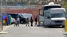 Migrantes de caravana abordan carros de ICE después de haber sido procesados en garita de San Ysidro