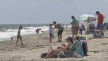 Algunas personas disfrutan las playas de Palm Beach Gardens a pesar de las advertencias por Dorian