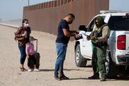 A Border Patrol agent inspects documents from a migrant family from Cuba after they the US-Mexico border and turned themselves to authorities on May 13, 2021 in Yuma, Arizona. - Apprehensions of undocumented immigrants at the US border with Mexico rose to a fresh 15-year high in April as the Biden administration failed to deter migrants, official data showed on May 11, 2021.US Customs and Border Protection reported it had interdicted 178,622 people trying to enter the United States without official immigration papers last month, up more than 5,000 from March's high numbers. (Photo by RINGO CHIU / AFP) (Photo by RINGO CHIU/AFP via Getty Images)