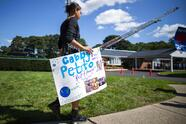 A woman carries a placard in honor of Petito as people attend the funeral service of Gabby Petito at Moloney's Funeral Home in Holbrook, N.Y. Sunday, Sept. 26, 2021. (AP Photo/Eduardo Munoz Alvarez)