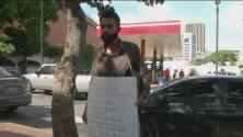 Con un cartel colgado, este profesor de matemáticas ofrece sus clases en las calles de Caracas, Venezuela