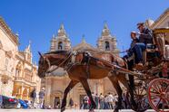 Mdina, Malta - March 27, 2017: Historical carriage in the city with tourists traveling by a horse on the town square of Saint Poul Cathedral in Europe