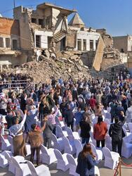 """People greet Pope Francis as he takes the podium at the square near the ruins of the Syriac Catholic Church of the Immaculate Conception (al-Tahira-l-Kubra), in the old city of Iraq's northern Mosul on March 7, 2021. - Pope Francis, on his historic Iraq tour, visits today Christian communities that endured the brutality of the Islamic State group until the jihadists' """"caliphate"""" was defeated three years ago (Photo by Zaid AL-OBEIDI / AFP) (Photo by ZAID AL-OBEIDI/AFP via Getty Images)"""