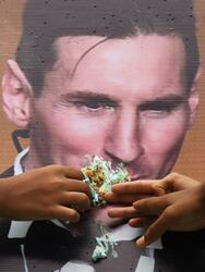 Indian football fans feed a piece of cake to a poster bearing the image of Argentine striker Lionel Messi during an event to celebrate his birthday in Kolkata on June 24, 2017. / AFP PHOTO / Dibyangshu SARKAR (Photo credit should read DIBYANGSHU SARKAR/AFP via Getty Images)