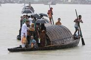 Boatmen carry commuters in the rain in River Sitalakkha in Narayangonj district, 16 kilometers (10 miles) east of Dhaka, Bangladesh, Monday, July 5, 2010. Over a dozen people are reported missing after a river ferry collided with a barge and capsized in the district Sunday night. (AP Photo/Pavel Rahman)